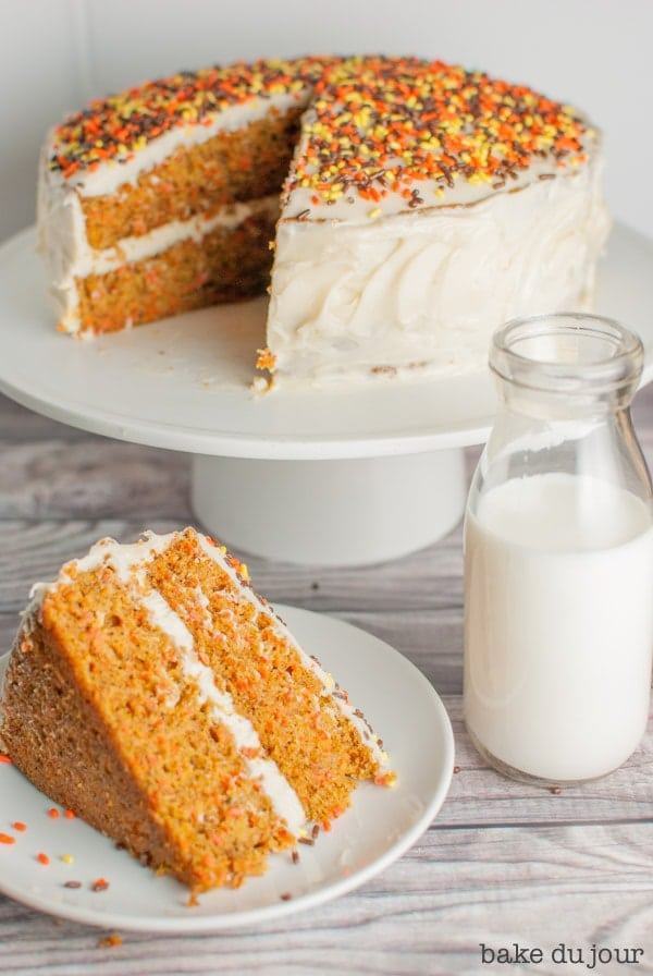 My Favorite Carrot Cake - a slice of carrot cake with the rest of the cake in the background on a cake stand