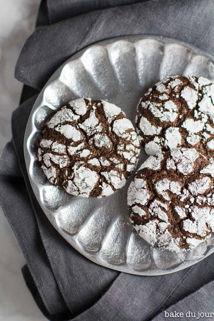 A set of 3 chocolate crinkle cookies on a silver plate