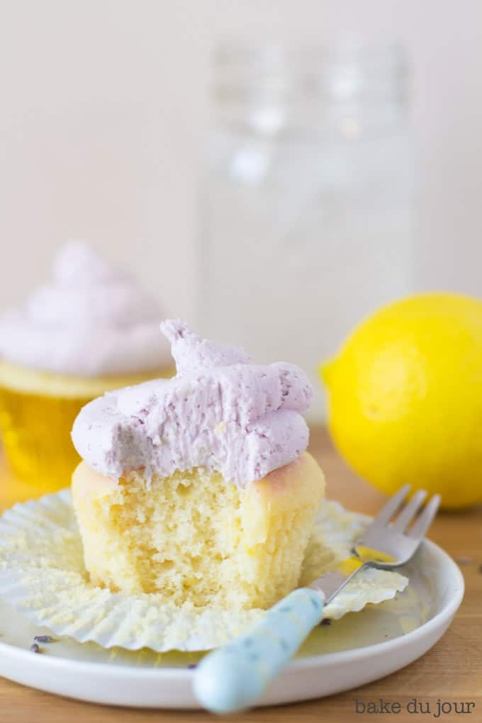 A Lemon Lavender Cupcake with a bite taken out of it
