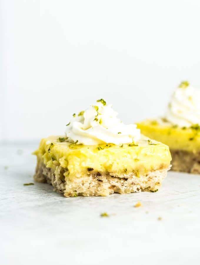 One Coconut Lime Bar topped with whipped cream and lime zest at the forefront, with another bar in the background