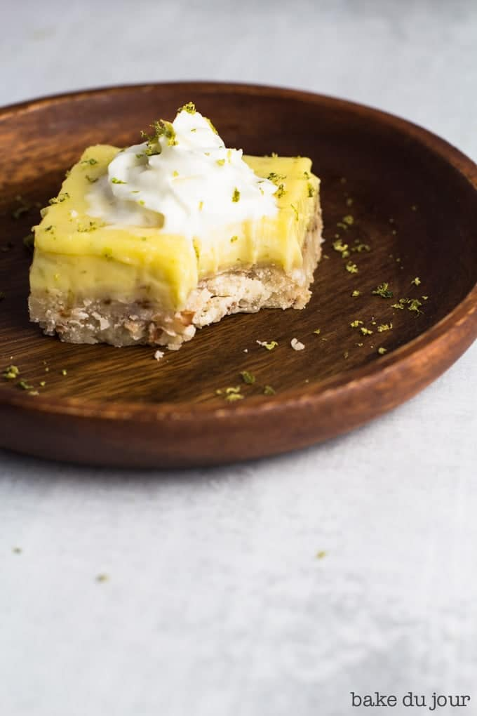 A serving of Coconut Lime Bar on a small wooden plate, with a bite taken out of it!