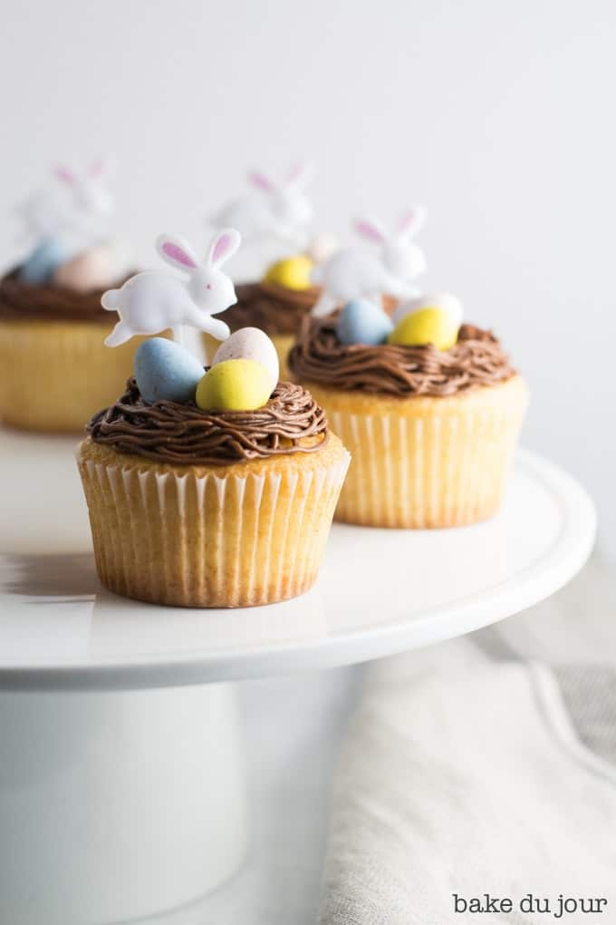 Four Easter Egg Cupcakes (yellow cake cupcakes topped with chocolate buttercream frosting, 3 Cadbury mini eggs, and an Easter bunny party pick) arranged in a semi-circle on a white cake stand