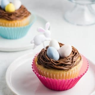 A yellow cake cupcake topped with chocolate buttercream frosting, three Cadbury mini eggs, and an Easter bunny party pick, with another cupcake in the background