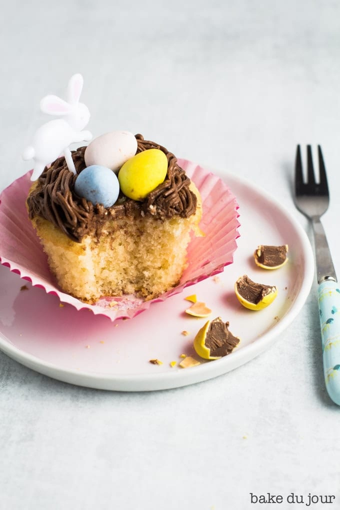 A yellow cake cupcake topped with chocolate buttercream frosting and an Easter bunny party pick on a white dessert plate, with a bite taken out of it. A light blue dessert fork placed on the right of the plate