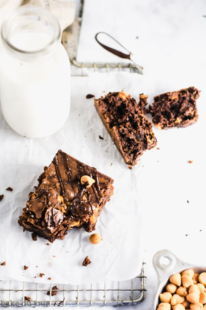 A brownie with a bite taken out of it with a jug of milk in the background